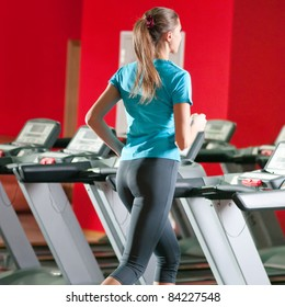 Young woman at the gym exercising. Run on on a machine.