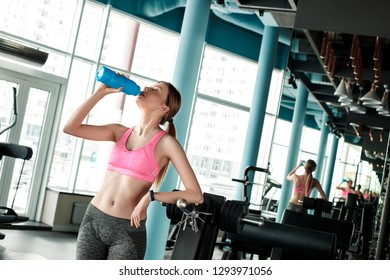 Young woman in gym healthy lifestyle standing holding bottle drinking water thirsty closed eyes relaxed