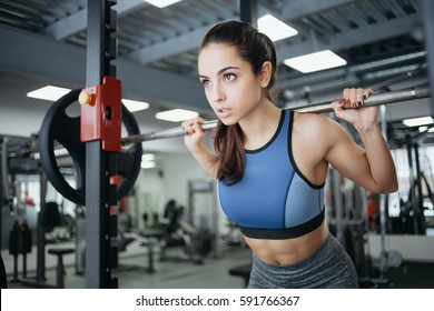 Young woman at the gym using fitness equipment. Sporty girl in blue top raising the bar and looking somewhere in front of her. She is working out intensively. Close up