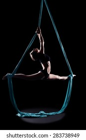 Young woman gymnast with blue gymnastic aerial silks isolated on black
