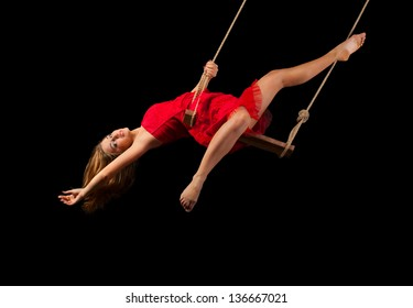 Young woman gymnast on rope on black background