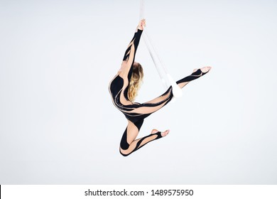 Young woman gymnast wearing black costume on trapeze on white background