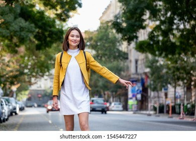 Young woman hailing a taxi ride. Beautiful charming woman hailing a taxi cab in the street. Businesswoman trying to hail a cab in the city. Tourist woman hailing a taxi