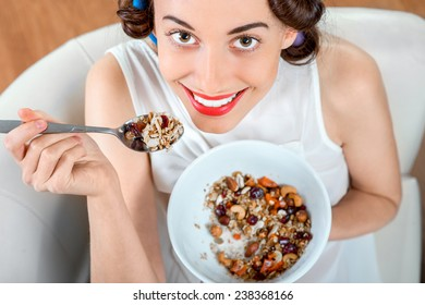 Young woman with hair curlers eating granola breakfast sitting on the couch at home
