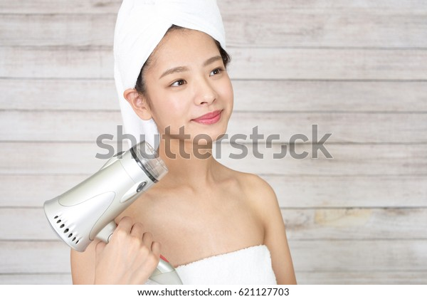 Young woman with a hair dryer