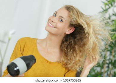 young woman with hair drying hair with electric blowdryer