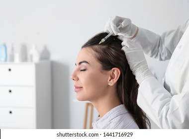 Young woman with hair loss problem receiving injection in salon