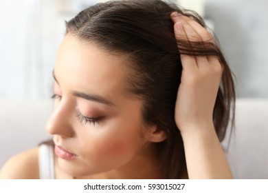 Young woman with hair loss problem at home, closeup