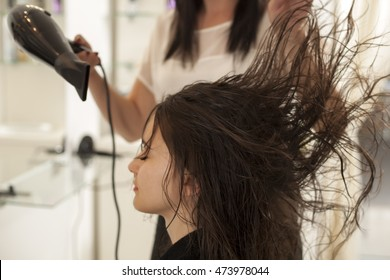 young woman in a hair salon. drying hair with hair dryer
