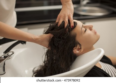 young woman in a hair salon enjoys while massaging her scalp