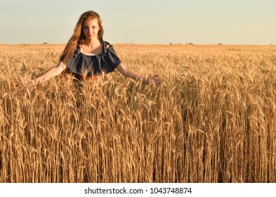 A young woman with hair untwisted standing in the field. She is surrounded by colostrum of rye, touches the stem, looks into the camera