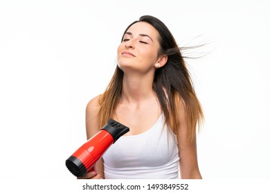 Young woman with hairdryer over isolated background