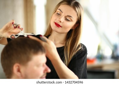 Young Woman Hairstylist Cutting Male Client Hair. Beautiful Hairdresser Holding Scissors for Haircut. Female Stylist Trimming Man Hairdo in Beauty Salon. Beautician Making Hairstyle for Guy Client