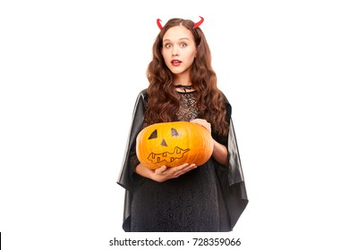 Young woman in Halloween costume posing against white background in studio