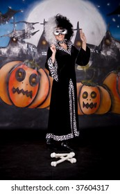 Young woman, Halloween lady impersonating Cruella de Vil. Studio, painted themed background.