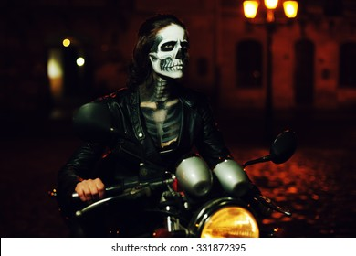 Young woman with Halloween makeup sitting on the motorbike . Street portrait. Close up
