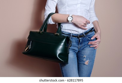 Young woman in hand big green trendy leather bag. Stylish accessory watch