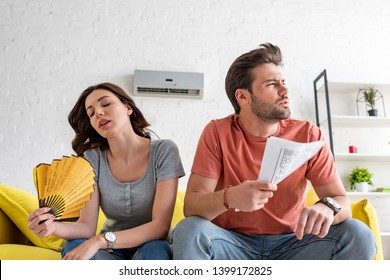 young woman with hand fan and handsome man with newspaper suffering from heat at home