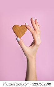 Young woman hand holding biscuit isolated on pink background.