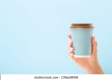 Young woman hand holding disposable paper cup on light blue background. Pastel color. Takeaway coffee or other drink. Closeup. Empty place for text. Front view.