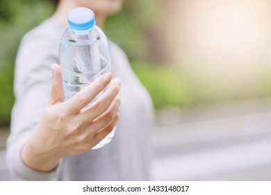 young woman hand holding give fresh drinking water bottle from a plastic in the park Morning sunlight. health care concept