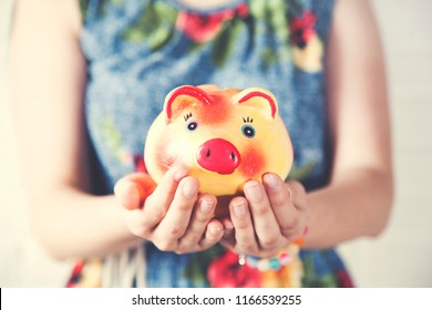 Young woman hand holding piggy bank