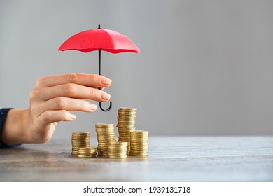 Young woman hand holding small red umbrella over pile of coins on table. Close up of stack of coins with female hands holding umbrella for protection. Financial safety and investment concept.   - Shutterstock ID 1939131718