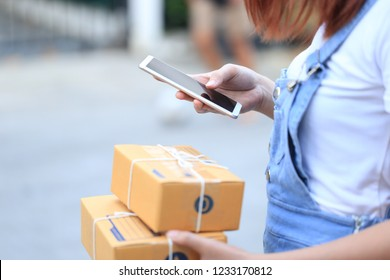 young woman hand holding smartphone and signing receipt of delivery package, shipping and postal service concept