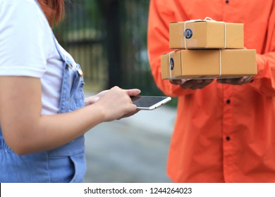 young woman hand holding smartphone and signing receipt of delivery package with delivery man bringing some package at the home, shipping and postal service concept