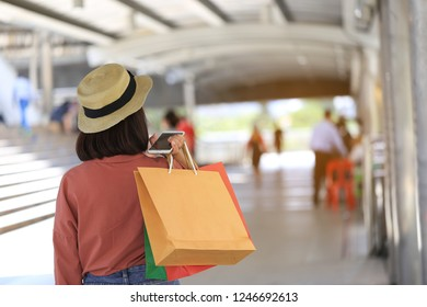young woman hand holding smartphone and shopping bags with standing at the department store