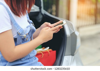 young woman hand holding smartphone and shopping bags with standing at the car parking lot, shopping concept