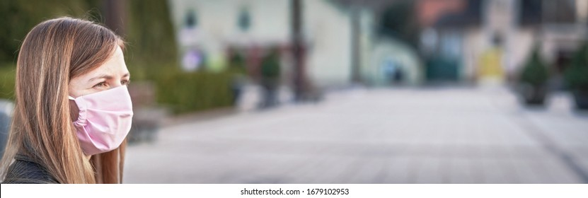 Young woman with hand made face nose mouth mask portrait, blurred empty city square behind her. Wide banner space for text - can be used during coronavirus covid19 outbreak prevention