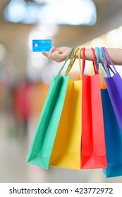 young woman hand with shopping bags and credit card.
