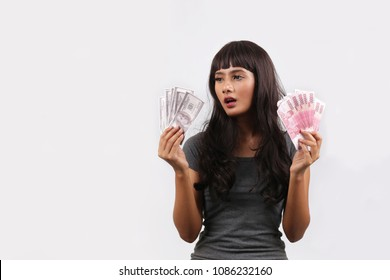young woman hand showing rupiah Indonesian money and US dollar. hand holding rupiah Indonesian money vs US dollar.