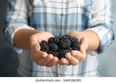 Young woman with handful of ripe blackberries, closeup