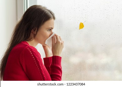 Young woman with handkerchief sneezes, stands near a rainy autumn window, cold season, copy space.