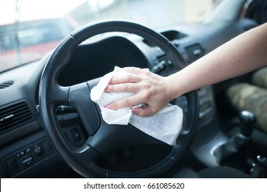 Young woman hands cleaning the interior of car by white rag / clothes