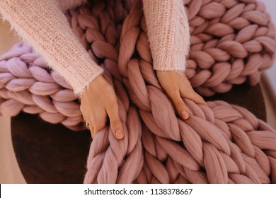 Young woman hands grab pink giant, large warm merino wool plaid blanket. Cozy morning