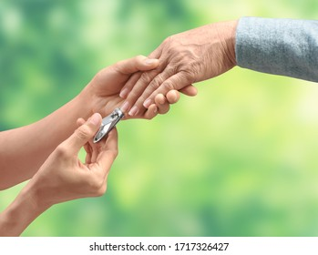 Young woman hands help cutting nails with nail clipper for Elderly woman is on green background
