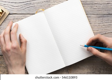 young woman hands hold opened notebook pages with blue pencil in light wooden table with bookmarks - Shutterstock ID 546110893