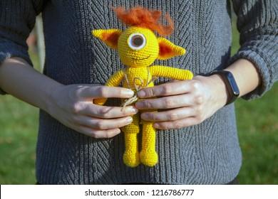 a young woman hands holding an amigurumi crochet cyclops monster