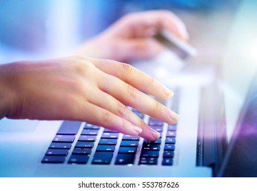 Young woman hands holding credit card and using laptop computer for Online shopping, e-shopping, ebanking. Person buying online in internet. E-banking concept.
