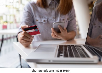 young woman hands holding credit card and using cell, smart phone for online shopping or reporting lost card, fraudulent transaction