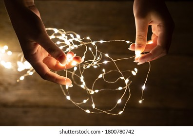 Young woman hands holding fairy lights.