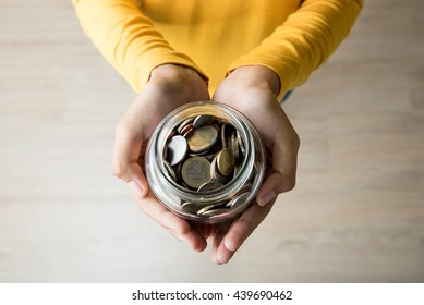 Young woman hands holding glass jar with coins inside - top view