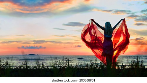 Young woman with hands up holding red scarf in wind on the beach