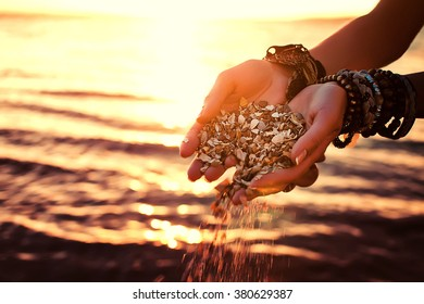 young woman hands holding sand on  exotical beach on sunset. natural vintage summer background