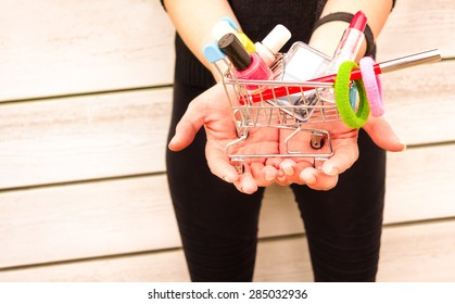 Young woman hands holding trolley with makeup objects and gadgets - Female vanity and shopping addiction - Girl with colorful beauty products on wooden background - Light pink vintage filter