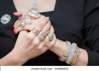 Young woman hands with multiple bracelets and fingers with many rings with diamond