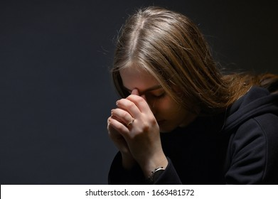 Young Woman Hands Praying in Dark